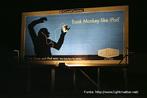 Foto de um billboard (outdoor) contendo a figura de um macaco utilizando um tocador de música.  Palavras-chave: animal, gorila, música, tecnologia, inferência.