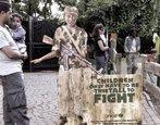 Foto mostrando a figura, produzida pela Unicef, de um menino soldado. O material é exposto em um local público, e um homem para a fim de observar.  Palavras-chave: classes de palavras, pronome, criança, soldado, parque.