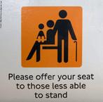 Foto de um cartaz solicitando a cessão de assentos a pessoas com dificuldade de ficar em pé. Infere-se a representação de um idoso de uma mulher com criança de colo. Palavras-chave: Placa. Cadeira. Transporte. Londres. Educação. Polite.
